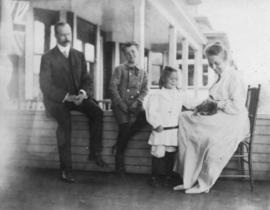 [Group portrait of L.D., Theodore, Kenneth and Annie Louise Taylor on a porch]
