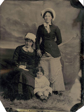 [Studio portrait of two young women and a child]
