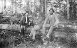 [Three men seated on log in forest]