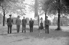 Group portrait of air force men, cadets and civilians standing around a flagpole