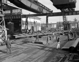 [Men using cranes to move large metal structures at Western Bridge and Steel Fabricators Ltd.]