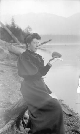 [Mrs. H.W. Maynard sitting on tree stump at beach near Brockton Point, Stanley Park]
