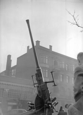 [Anti-aircraft gun in front of stores and apartment building on Georgia Street]
