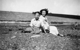 Mrs. Chan and one of her sons sitting on a beach by English Bay