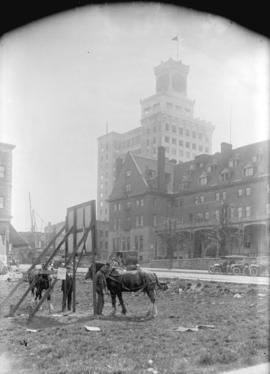 [View of Georgia Street near Granville Street, showing Hotel Vancouver, and men with horses in em...