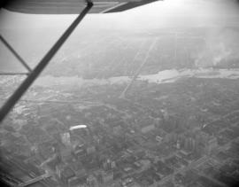 [Aerial view of Vancouver showing the Goodyear blimp above the Downtown area]