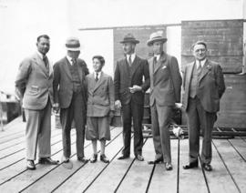 [Group portrait of L.D. Taylor standing on a large shipping dock or pier with a boy and four men]