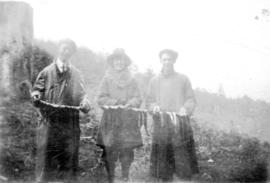 Two men and a woman holding caught fish