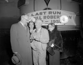 "[Group gathered in front of a train with a sign stating ""Last Run, Bill Robertson""]"