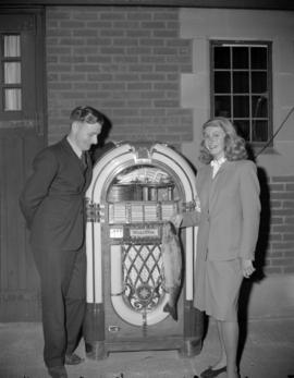 [Man and woman holding a fish standing in front of a juke-box at the Red Cross cancer drive]