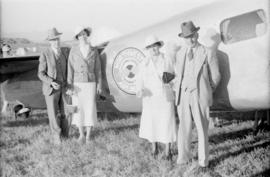 [Two couples beside a] Northwest Airlines airplane