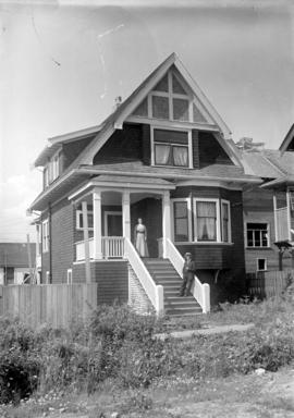 [Man and woman standing on front steps of house in Grandview-Cedar Cottage area]