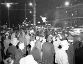 [An unidentified street at night filled with people]