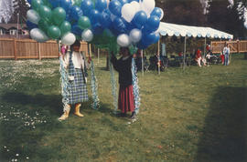 Commissioner and helper holding Centennial balloons