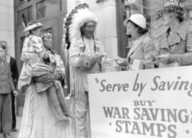 [Stoney Indians buying war savings stamps from two woman in a war savings booth on the street]