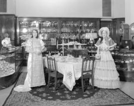 [Models in period costumes display 'Community Plate' in the china and silverware depart...