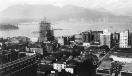 [View of downtown Vancouver and waterfront from above, showing Marine Building under construction]