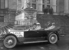 "[Four men in open car with sign ""Love Special""  - silent film star Wally Reid on visit ..."