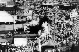 Amusement rides, tents, and crowd in P.N.E. Playland