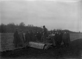 Man standing on a tractor talking to a group of men