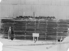"Man standing beside building supplies; sign reads ""200 tons  test"""