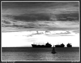 Evening anchorage [3 large ships and small sailboat in harbour at sunset]