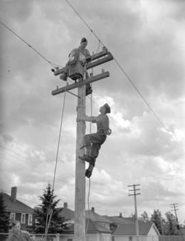 [Men climbing a utility pole near a] Calgary trade school