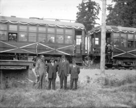 [Engineer, conductor and motormen standing outside interurban railway cars for opening of the Saa...