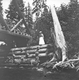 [Woman standing at edge of Capilano Creek Bridge at Keith Road]