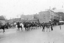 [A parade of men on horses and bicycles on Georgia Street at Howe Street]