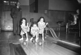 [Three young girls bowling]