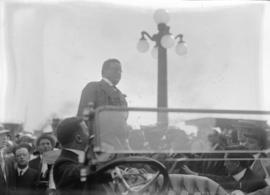 President Roosevelt standing in back seat of car