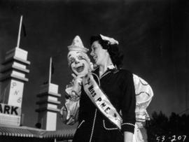 Miss P.N.E., Lynn Adcock, posing with clown at main gates to Exhibition Park