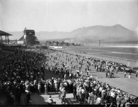 Crowd watching horse race, with Grandstand and Shoot the Chutes ride in background