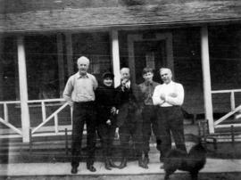 [L.D. Taylor standing in front of an inn at Summit Lake with unidentified men, a woman and a dog]