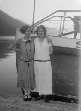 Two women on a dock next to a boat