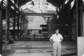 Construction of new warehouse, man in white shirt standing in foreground