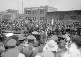 Large crowd gathered around automobile, men in military uniforms