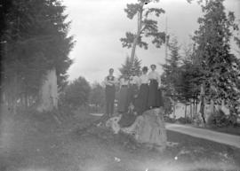[Family assembled on rock near road in Stanley Park]