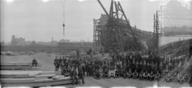 [An unidentified group in front of a wooden ship under construction at Western Canada Shipyards, ...
