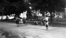 Children playing double dutch [jump rope] on the street