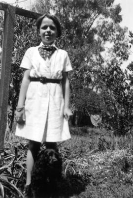 [Mary Louise Taylor standing in yard with her dog]