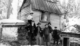[Unidentified group in front of cabin]