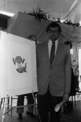 Michael Francis beside a drawing of the official Centennial mascot Tillicum
