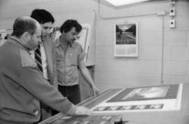 Toni Onley, Robert Dubberley and unidentified man examine Centennial Art Series print at Agency P...
