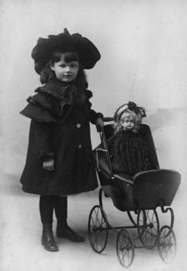 Portrait of Olga Jenkinson Bell as a child with doll carriage