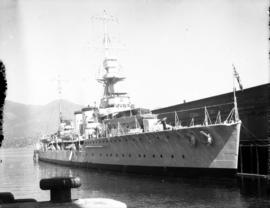 "Royal Navy light cruiser, possibly ""H.M.S. Danae"" at berth"