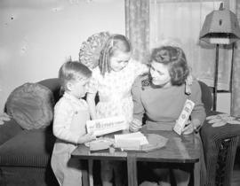 Mrs. Gordon Egart and children [looking at Victory Bonds]