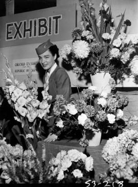Model dressed as stewardess with Flowers by Air exhibit in horticultural show, P.N.E. Forum