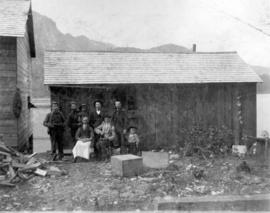 [Unidentified men, children and building in Port Moody]